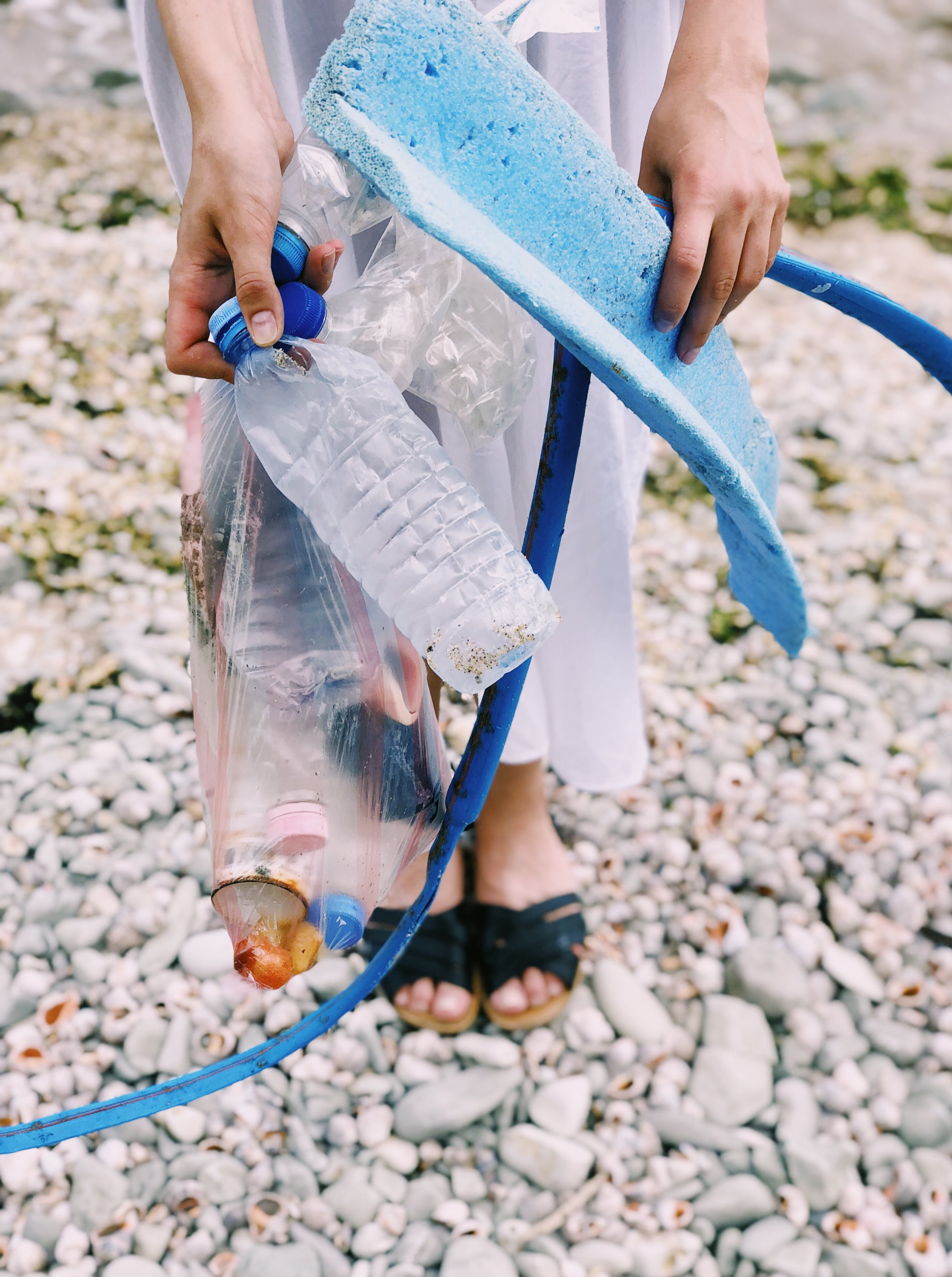 Beach clean up, lady holding plastic litter